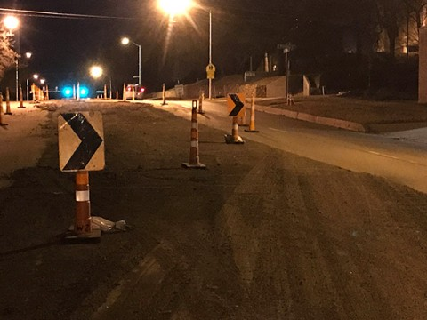 streetlights light up a construction zone with orange cones