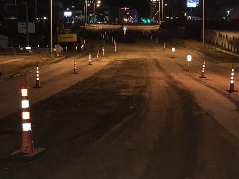 construction zone at night with glowing orange cones