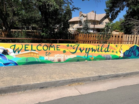 """welcome to Ivywild"" mural with scenes from Colorado Springs such a bear in the mountains, a baseball player, and the broadmoor"