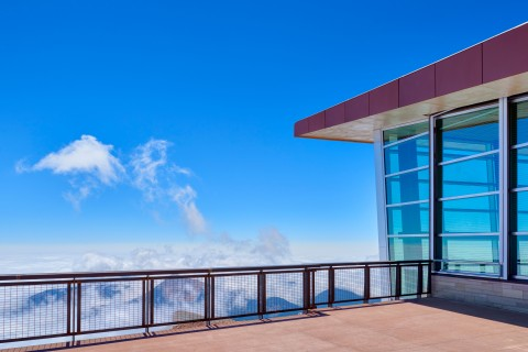 outdoor viewing platform. To the right is a wall of windows of the visitor center. To the font is the railing of the platform. Beyond that mountains and clouds can be seen below.