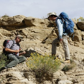 two men look for fossils along rock formations