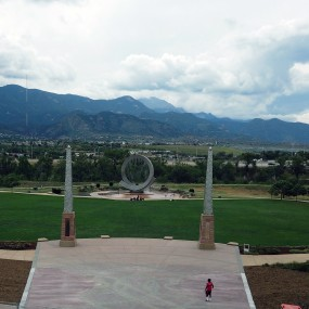 view of america the beautiful park from the bridge. large grassy area. two large pillars at entrance of grass. Circular fountain in the background. Pikes Peak in the background.