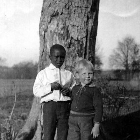 A historic black and white photo of a young African American boy and a Caucasian boy