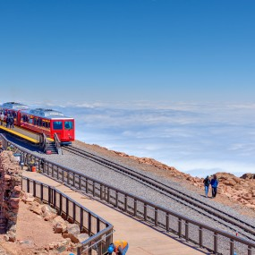 looking down on the COG Railroad at the summit of pikes peak. The train is bright red. Clouds below obscure the landscape.