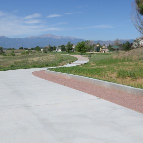 new concrete trail with park and pikes peak in the background