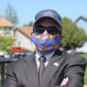 Mayor John Suthers wearing a Colorado cloth facemask, sunglasses, and a blue Olympic City USA hat