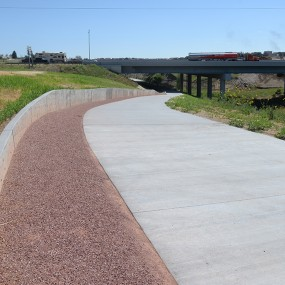 new cement trail with bridge in the background.