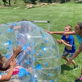 """officer in a large plastic """"bubble"""" and kids are rolling him around"""