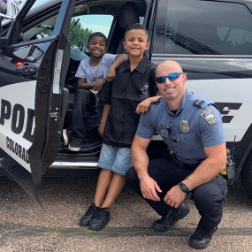 kids and officer pose for photo next to police car