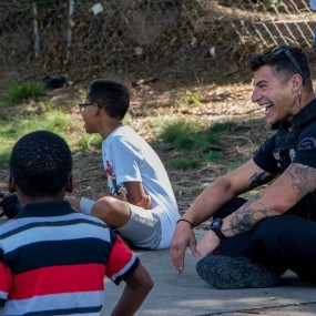officer sitting on ground laughing with kids