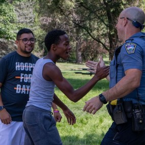 young black teenage boy gives officer a high five
