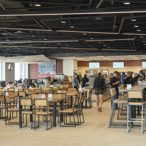 people milling about and eating in the dinging hall. There are three rows of tables and chairs.