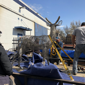 workers loading repaired deer onto truck for transportation to installation site