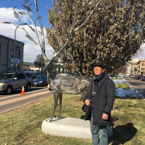 artist standing next to repaired deer after installation on a media downtown.