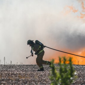 firefighter pulling hose with smoke and fire in the background