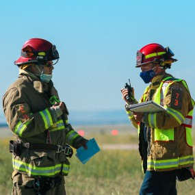 two people in firefighter coats, face masks, and helmets talking