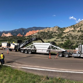 paving crews repairing a large section of road. Garden of the Gods park in the background.
