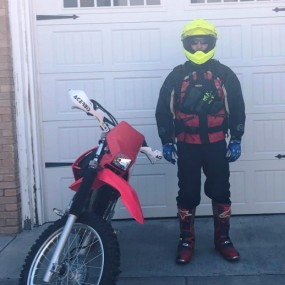 red motorbike and firefighter in red jacket, boots and yellow helmet