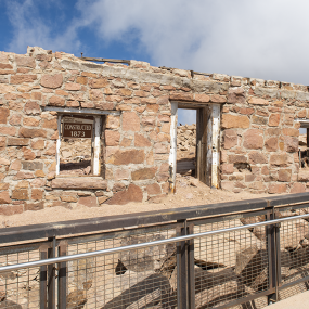 """remains of a brick wall with two windows and a doorway. A sign in the window says """"Original summit house>"""
