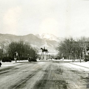 historic black and white image of Platte avenue with the statue of General Palmer in the middle of the intersection with Pikes Peak in the background. The streets and mountain are snow covered.