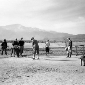 historic photo. people playing golf. The land is flat with no trees. Pikes Peak in the background.