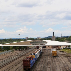 View of the entire bridge looking north over the rail yard. The interlocking loops create an oval gap in the walls so you can see through the sides of the bridge in the center. the shape is flat on the bottom (the walkway) and the side rise to a sloped pe