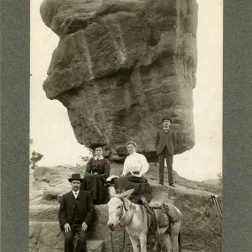 historic black and white photo of two men and two women in 1908 period clothing and a donkey in front of Balanced Rock at Garden of the Gods