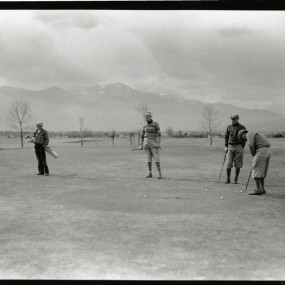 historic photo. people walking on golf course. pikes peak in the background. A few small trees with no leaves are on the course.