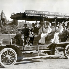 Historic black and white photo of a 1909 old fashioned open air bus touring through Garden of the Gods
