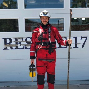 Swift water rescue uniform includes a red wet suit, life vest, whistle, knife and throw rope
