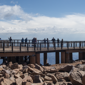 boulders with an elevated walkway beyond. People are standing and looking across the expanse on the other side.