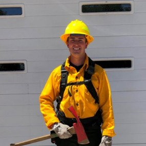 Wildland firefighting uniform: long sleeve yellow shirt, yellow helmet, green pants and ax