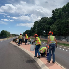 workers in yellow safety vests clean up garbage from a narrow cement median