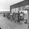 students stand in a line. Each student has a bike