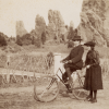 General William Jackson Palmer sits on a bicycle. Dorothy Palmer stands in back of him, holding the bicycle seat.