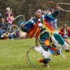 A Native American hoop dancer in bright color costume