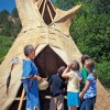 Docent showing children a teepee