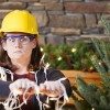 lady in a hard hat tangled up in a string of holiday lights