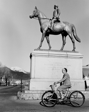 woman riding past the palmer on a horse statue.