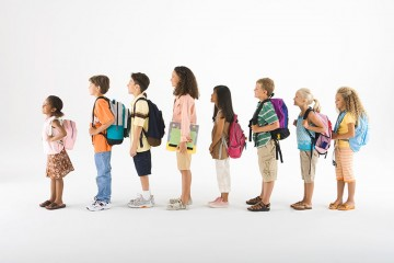 School kids lined up wearing back packs