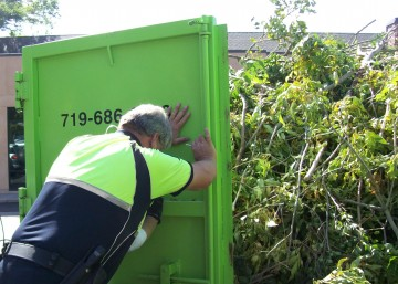 Code Officer helping close dumpster