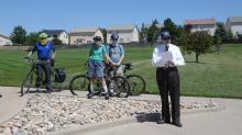 Mayor Suthers speaking with three bike riders standing behind him.
