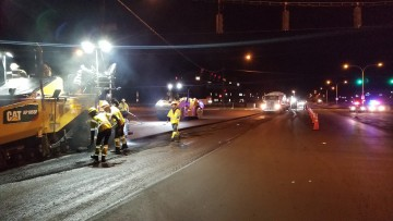 people and asphalt roller working on briargate parkway at night