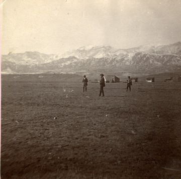 black and white photo of people walking in a flat, treeless plain with mountains in the background.
