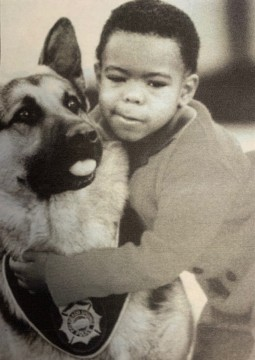 a young boy hugs a German shepherd dog that is wearing a police badge patch around its neck.