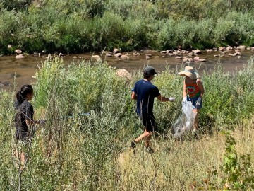 photo of students picking up trash in creek