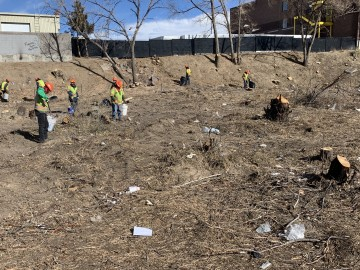 crews in safety vests and hard hats clean up trash in an open space