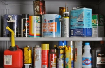two shelves with various paint cans, cleaners, gas containers and other hazardous materials