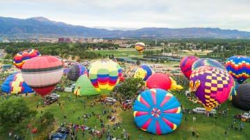 aerial view of Memorial Park where hot air balloons are getting ready to take off. Pike Peak is in the background.