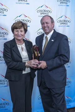 Mary Ellen McNally and Mayor John Suthers holding award